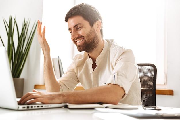 Изображение привлекательного бизнесмена 30-х годов в белой рубашке, работающего с ноутбуком и бумажными документами, сидя в ярком офисе
