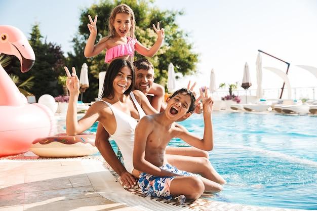 ホテルの外にピンクのゴム製のリングが付いている豪華なスイミングプールの近くに座っている子供たちと魅力的な白人家族の画像