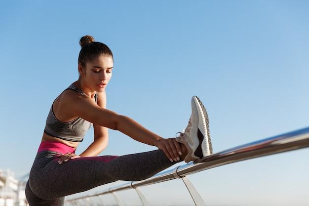 桟橋での魅力的なフィットフィットネスガールワークアウトの画像