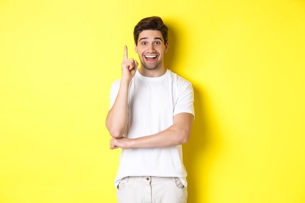 アイデアを持って、指を上げて計画を提案し、興奮して笑って、黄色の背景の上に立っている魅力的な男の画像。