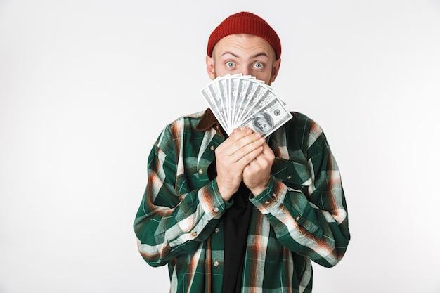 흰색 배경 위에 격리 된 서있는 동안 달러 돈의 팬을 들고 격자 무늬 셔츠를 입고 매력적인 남자의 이미지