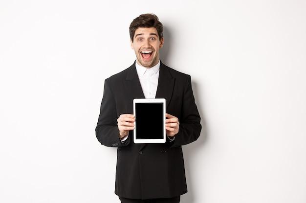 トレンディなスーツを着た魅力的な男性起業家の画像。デジタルタブレットの画面を表示し、白い背景の上に立って驚いて笑っています。