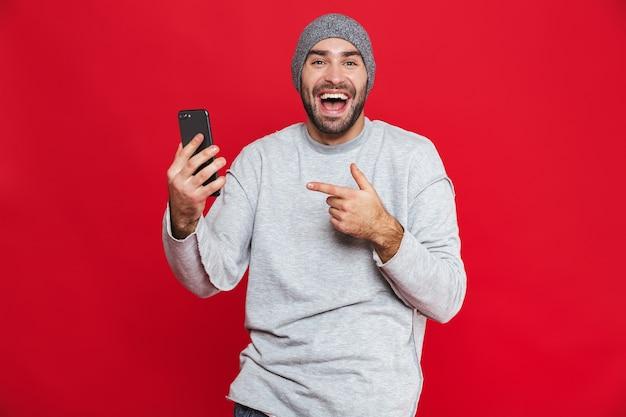 매력적인 남자 30 대 수염과 콧수염 서있는 동안 스마트 폰을 들고 격리 된 이미지