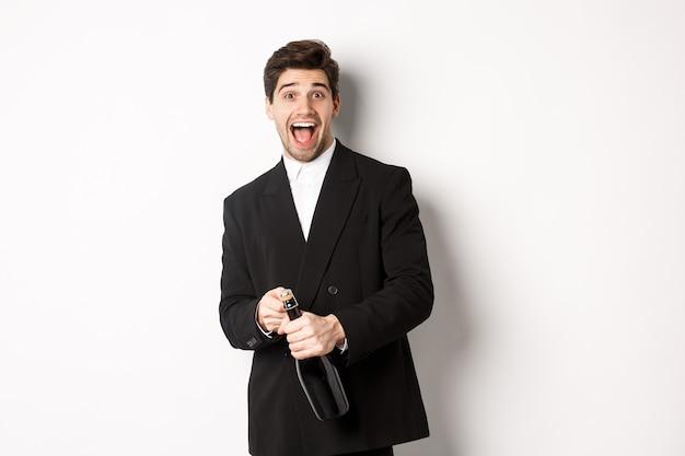 パーティーを開いて、新年を祝い、シャンパンのボトルを開けて、白い背景に幸せに立っている黒いスーツを着た魅力的な男性の画像