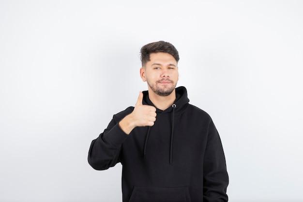 흰 벽 위에 절연 미소로 카메라에 엄지 손가락을 보여주는 매력적인 남자의 이미지