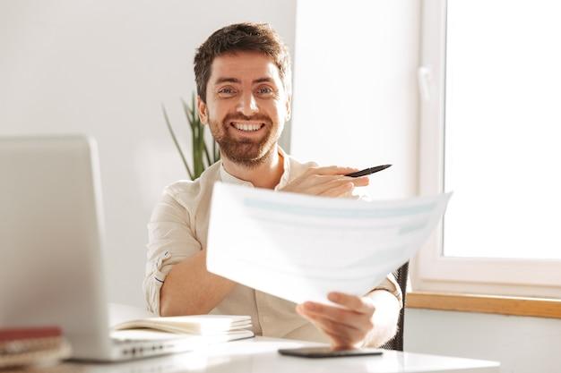 Изображение привлекательного офисного парня 30-х годов в белой рубашке с ноутбуком и бумажными документами во время работы на современном рабочем месте