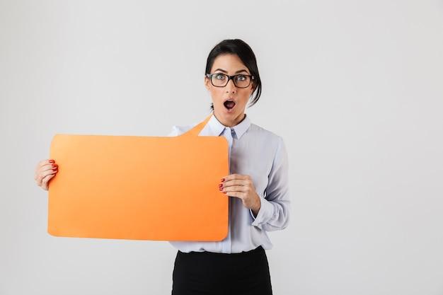 흰 벽 위에 절연 노란색 copyspace 현수막을 들고 안경을 쓰고 매력적인 사무실 여자의 이미지