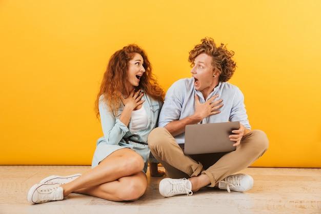 黄色の背景で隔離、床に座って銀のラップトップを使用して魅力的な楽観的なカップルの男性と女性の画像