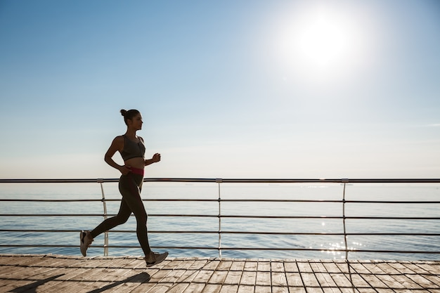 海の近くで一人でジョギングしている魅力的なスポーツ選手の画像。