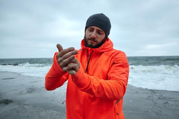 灰色の荒天で海辺に立って、暖かいスポーティな服を着て、朝のトレーニングの準備をしているひげを持つ魅力的な若い運動ブルネットの男性の画像