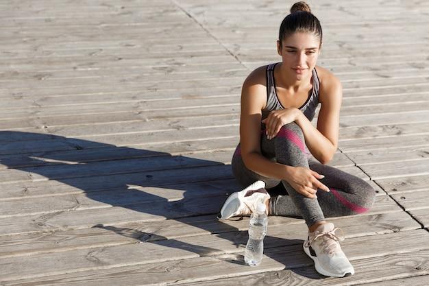 トレーニング後に休憩をとっている魅力的な若い女性アスリートの画像