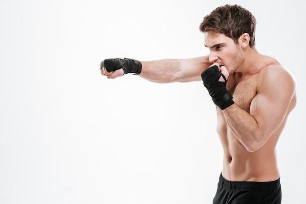 Изображение привлекательного боксера молодого человека делают упражнения бокса над белой стеной. посмотри в сторону.