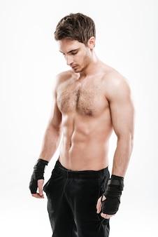 Изображение привлекательного боксера молодого человека, стоящего над белой стеной. посмотри в сторону.