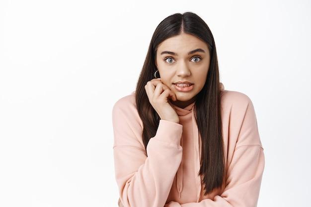 ぎこちない若いブルネットの女性が身をかがめて有罪に見え、愚かな小さな間違いを犯し、白い壁の上に立っている画像