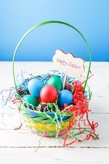 幸せなイースターを願って木製のテーブルの上の空の青い壁にカラフルな卵とバスケットの画像