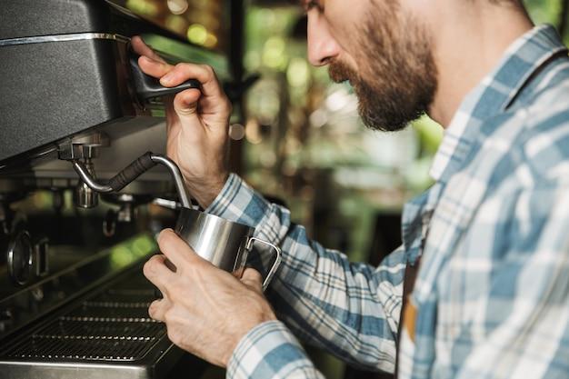 屋外のカフェや喫茶店で働いているときにコーヒーを作るエプロンを着ているひげを生やしたバリスタの男性の画像