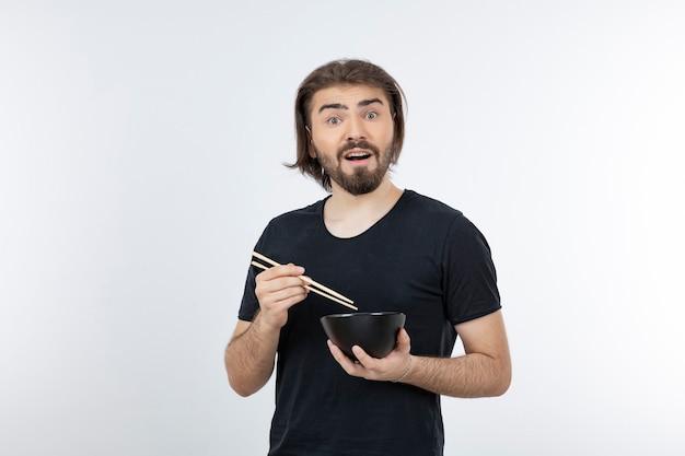 흰 벽에 젓가락으로 그릇을 들고 수염 된 남자의 이미지.