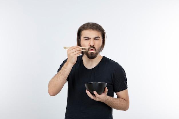 白い壁に箸でボウルを持っているひげを生やした男の画像。