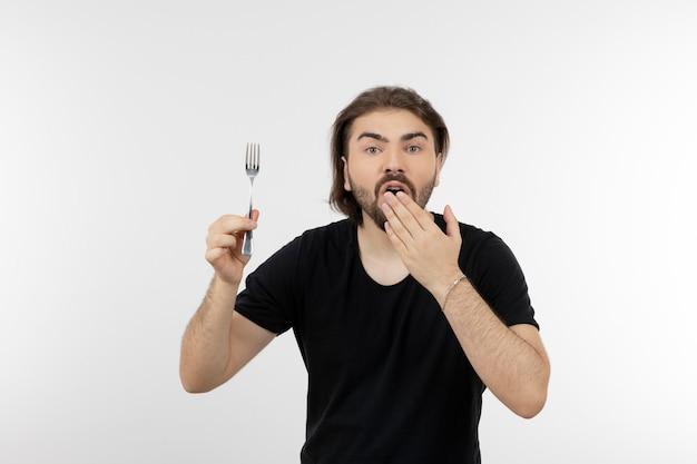 흰 벽에 포크를 들고 수염 난된 남자의 이미지.