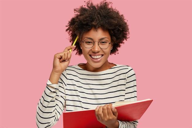 이빨 미소로 아름다운 명랑 소녀의 이미지는 연필로 노트에 메모를 씁니다.
