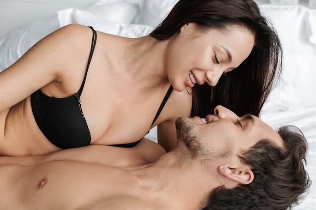 집이나 호텔 아파트에서 침대에 누워있는 동안 아름다운 커플 남자와 여자가 함께 키스의 이미지