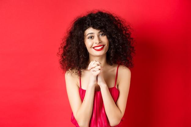 빨간 드레스와 메이크업에 아름 다운 곱슬 머리 여자의 이미지, 감사 인사, 카메라, 스튜디오 배경에서 행복 하 게 웃 고 감사합니다.