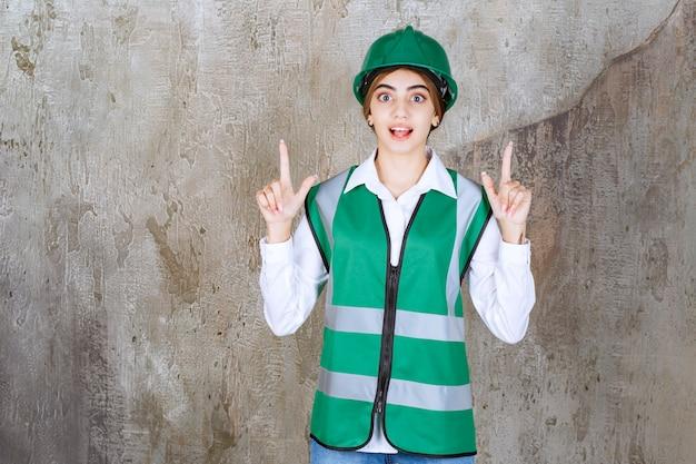 何かを指している緑のヘルメットの美しい女性建築家の画像