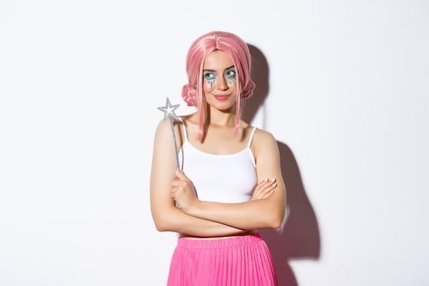 Изображение красивой девушки, одетой как фея в розовом парике, держащей волшебную палочку и улыбающейся, празднующей хэллоуин.