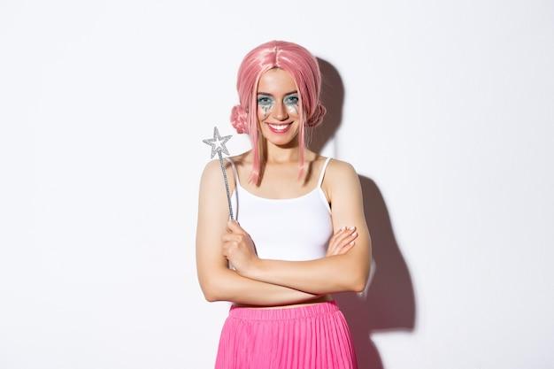 ピンクのかつらの妖精に扮した、魔法の杖を持って笑顔でハロウィーンを祝う美しい少女の画像。
