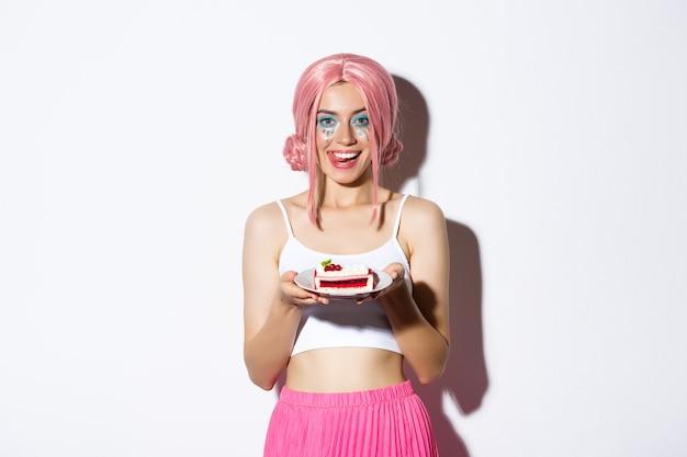 ピンクのかつらで、おいしいケーキを持って唇をなめ、何かを祝って、立っている美しい少女の画像。