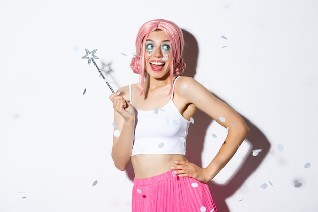 魔法の杖を持って踊る妖精の衣装でハロウィーンを祝う美しい幸せな女性の画像...