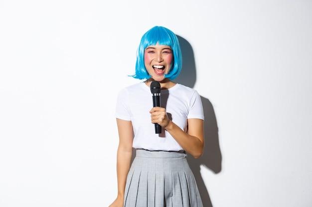 블루 애니메이션 가발, 마이크에 노래방 노래, 행복 미소, 서있는 아름다운 일본 여자의 이미지.