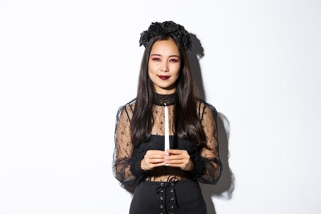 Изображение красивой женщины, празднующей хэллоуин в костюме ведьмы, держащей свечу и подозрительно косящейся на камеру, стоя на белом фоне.