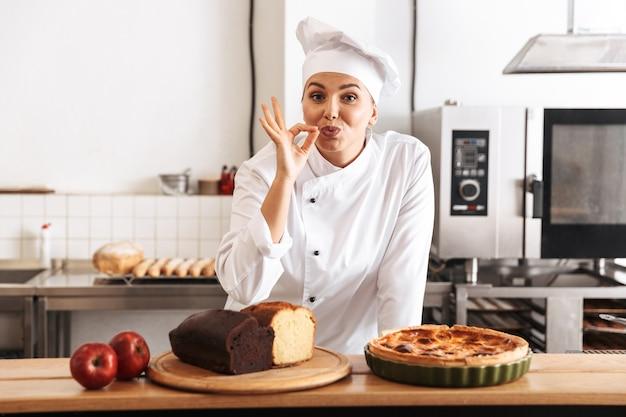 Изображение красивой женщины-шеф-повара в белой форме, позирующей на кухне в кафе с выпечкой