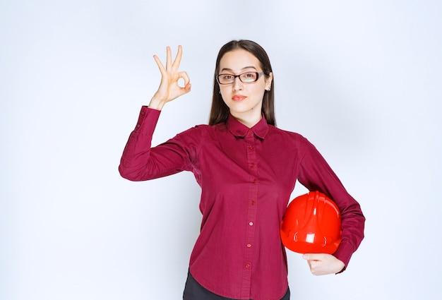 クラッシュヘルメットを保持し、okジェスチャーを示す眼鏡をかけた美しい女性の画像。