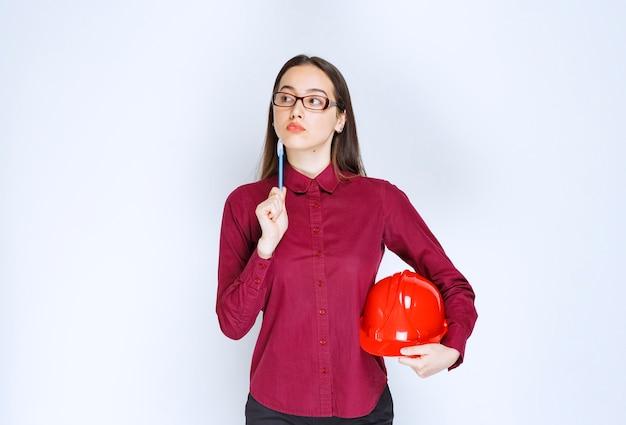 クラッシュヘルメットを保持しているメガネの美しい女性の画像。