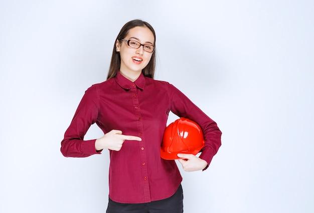 クラッシュヘルメットを指している眼鏡の美しい女性の画像。