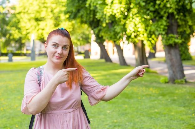 公園に滞在して指さしている美女の画像。夏の日の赤毛の女の子