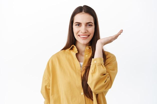 누드 천연 화장과 하얀 미소를 가진 아름다운 여성의 이미지, 얼굴의 절반을 벌리고, 손을 멀리 움직이고 효과 전후, 흰 벽 위에 서 있는 앞을 바라보는 이미지