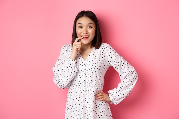 ピンクの背景の上に立って、誘惑と驚きを見つめて、ドレスを着て、指を噛み、笑顔で、何かを購入したい美しい若い女性の画像。