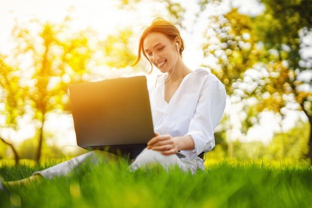 야외 공원에서 공부나 일을 위해 노트북 컴퓨터를 사용하는 아름다운 젊고 예쁜 빨간 머리 여성의 이미지