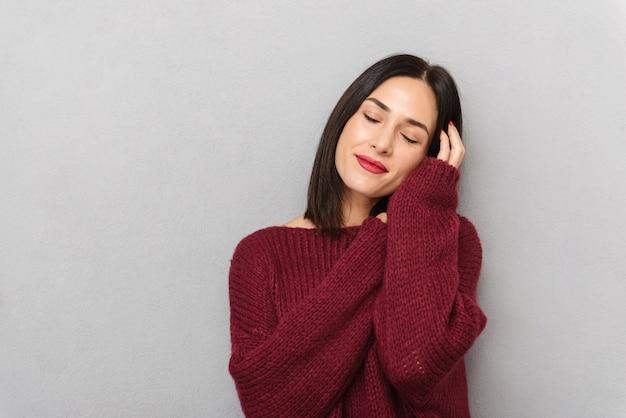 Изображение красивой молодой женщины, одетой в бордовый свитер, позирует изолированно.