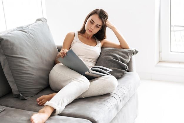 Изображение красивой молодой женщины, сидя на диване в помещении дома, читая книгу.