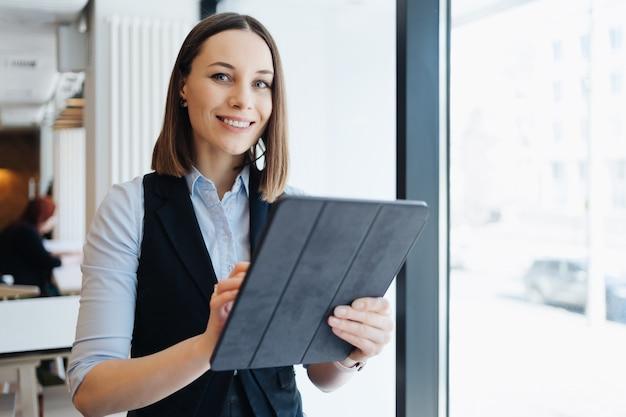 Изображение красивой молодой женщины, сидящей, держа в руках цифровой планшет. владелец бизнеса, кафетерий, ресторан