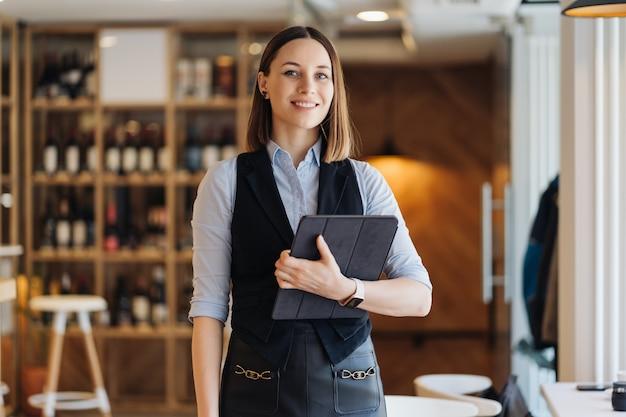 Изображение красивой молодой женщины, стоящей, держа в руках цифровой планшет. владелец бизнеса, кафетерий, ресторан