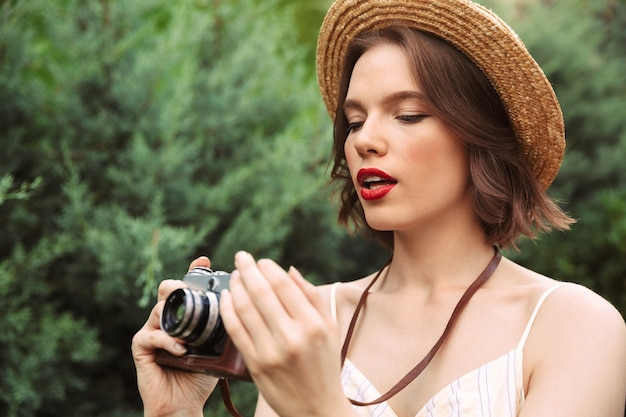 屋外でレトロなカメラを使用してドレスと麦わら帽子の美女の画像