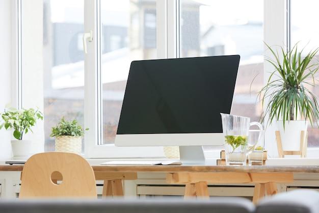 オフィスの木製テーブルに大きなコンピューターモニターの画像