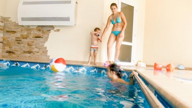 家の屋内プールで泳いでいる大家族の画像