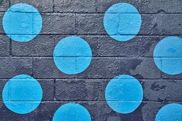 青い円でまっすぐに黒く塗られたセメント壁の画像