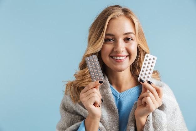 丸薬を保持している毛布に包まれた20代の金髪女性の画像